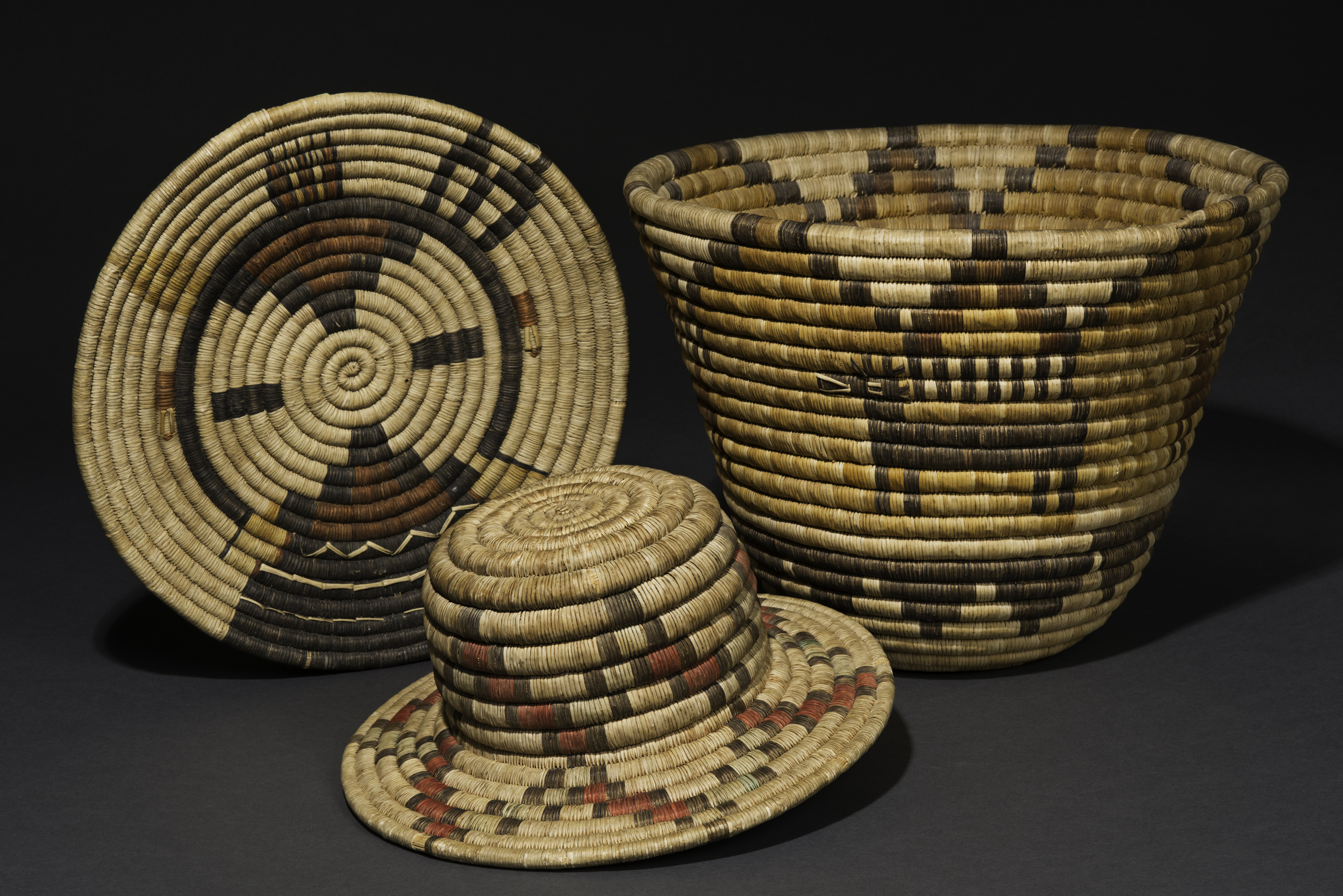 Coiled baskets from Second Mesa; yucca and galleta grass. Left to right: Hiilili katsina plaque, ca. 1975;  Novelty hat, ca. 1920;  Bowl with antelope and cloud design, ca. 1945. Gifts of Judith and Andrew Finger, 2018