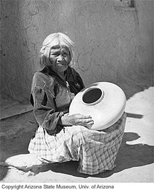 Nampeyo in her mid-70s holding a vessel she has just made. Photo by Tad Nichols, 1935.
