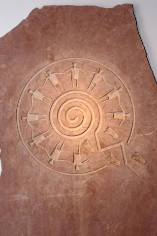 This image is of a sandstone-carved symbol illustrating the paths of life concept, with hand-holding figures standing in a circle above a spiraliform maze. The piece is by Hopi artist Gerald Dawavendewa.