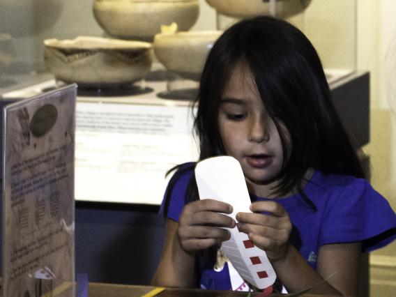 This image shows a young girl participating in hands-on activities