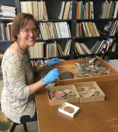 This is an image of Dr. Suzanne L. Eckert, head of collections. She is sorting pottery sherds.